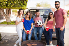 Group of friends hanging out at a soccer game. Five attractive young friends grilling some burgers and drinking beer while tailgating at a soccer game royalty free stock photo