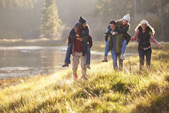 Group of friends have fun piggybacking by a lake Royalty Free Stock Image