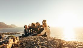 Multiracial group of friends enjoying and partying outdoors. Group of friends having beers while sitting on mountain top during sunset. Multiracial men and women stock images
