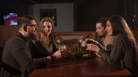 Group of friends having dinner at cafe. Two men and women are having fun together in a bar. They are drinking cocktails and talking happily stock video