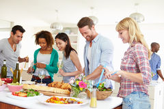 Group Of Friends Having Dinner Party At Home. Looking At Food Whilst Chatting Stock Photography