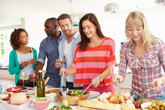 Group Of Friends Having Dinner Party At Home. Preparing Food In Kitchen Stock Photos