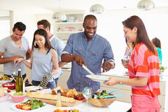 Group Of Friends Having Dinner Party At Home. Serving Up Food In Kitchen Whilst Having A Good Time Stock Images