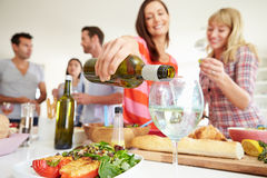 Group Of Friends Having Dinner Party At Home. With Woman Pouring Glass Of White Wine Royalty Free Stock Image