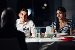 Group of friends having a dinner in a restaurant.Double date.Attractive people night out,dining in a hotel.Trendy people stock photography