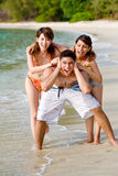 Group of friends having fun. Group of friends teasing and pulling ears of the guy by the beach Royalty Free Stock Images