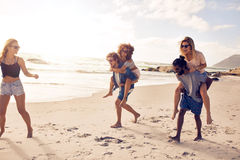 Group of friends having fun on the beach. Vacation, men piggybacking women Stock Image
