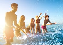 Group of friends having fun at the beach with water sea stock images