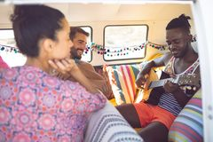 Group of friends having fun in a camper van at beach. Closed-up of happy group of diverse friends having fun in a camper van at beach royalty free stock images