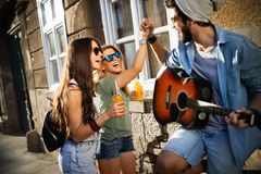 Group of friends having fun and hanging out outdoors. At summer stock image