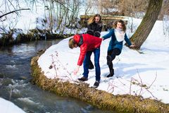 Group of friends having fun in the park in winter near the river royalty free stock photo