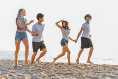Group of friends having fun running down the beach at sunset. royalty free stock photo