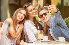 Group of friends having fun with a smart phone Royalty Free Stock Images