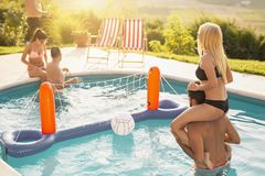 Friends playing volleyball in a swimming pool stock images