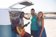 Group of friends having fun together near camper van at beach. Front view of happy group of diverse friends having fun together near camper van at beach royalty free stock image