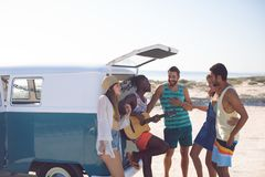 Group of friends having fun together near camper van at beach. Side view of happy group of diverse friends having fun together near camper van at beach royalty free stock photos