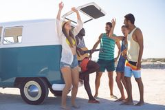 Group of friends having fun together near camper van at beach. Side view of happy group of diverse friends having fun together near camper van at beach stock images