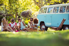 Group of friends having fun together near campervan. In park stock photo