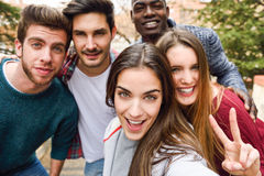 Group of friends having fun together outdoors. Group of multi-ethnic young people having fun together outdoors Royalty Free Stock Photos