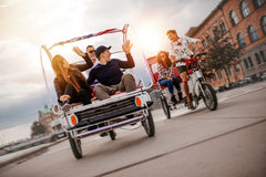 Group of friends having fun with two tricycles on road Stock Photo