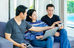 Group of friends having fun and using digital device mobile,lap. Top,tablet at home,Friendship concept Stock Image