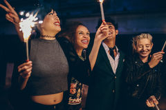 Group of friends having night party with sparklers Stock Images