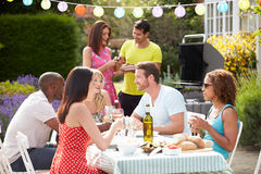 Group Of Friends Having Outdoor Barbeque At Home. In The Garden Eating Food Stock Photos