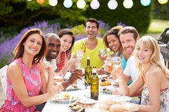Group Of Friends Having Outdoor Barbeque At Home. Holding Glass Of Wine Smiling To Camera Stock Images