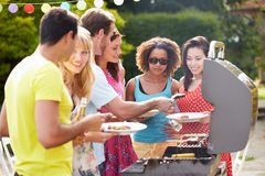 Group Of Friends Having Outdoor Barbeque At Home. Holding Plates With Food On Smiling Royalty Free Stock Image