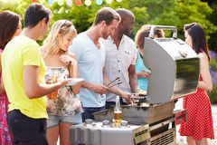 Group Of Friends Having Outdoor Barbeque At Home. Serving Food In Summertime Stock Photos