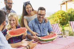 People eating watermelon at backyard party royalty free stock photography
