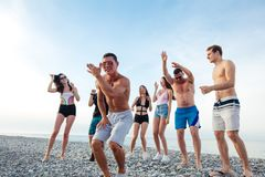 Friends dance on beach under sunset sunlight, having fun, happy, enjoy. Group of Friends Having Party on Beach, dance, jump and fun royalty free stock image