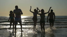 Group of friends having party in the ocean and run towards the beach at sunset in slow motion stock footage