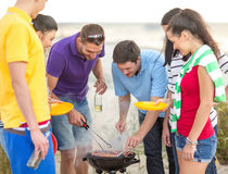 Group of friends having picnic on the beach. Summer, holidays, vacation, happy people concept - group of friends having picnic and making barbecue on the beach royalty free stock photo