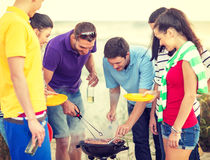 Group of friends having picnic on the beach. Summer, holidays, vacation, happy people concept - group of friends having picnic and making barbecue on the beach royalty free stock photography