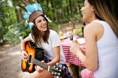 Group of friends having a picnic in a park outdoor. Happy young people enjoying bbq. Playing guitar, singing and drinking royalty free stock images
