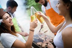 Group of friends having a picnic in a park outdoor. Happy young people enjoying bbq stock photography