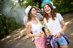 Group of friends having a picnic in a park outdoor. Happy young people enjoying bbq. Playing guitar, singing and drinking royalty free stock photography