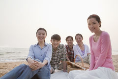 Group of Friends Having a Picnic by the Sea Stock Photo