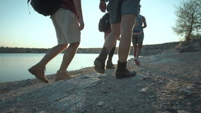Group of friends hiking on rocky coastline stock video