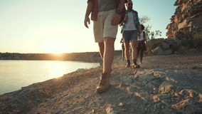 Group of friends hiking on rocky coastline stock video footage