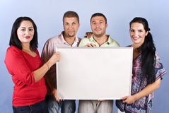 Group of friends hold a blank banner. Four friends standing in a line and holding a blank banner for presentation on blue background,check also People with blank Royalty Free Stock Images