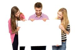 Group of friends holding blank paper. Three young people over white background Royalty Free Stock Photo