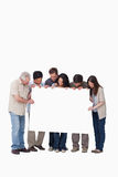 Group of friends holding blank sign together. Against a white background Royalty Free Stock Image