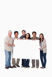 Group of friends holding blank sign together. Smiling group of friends holding blank sign together against a white background Royalty Free Stock Photos