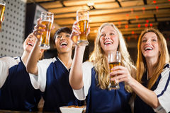 Group of friends holding glass of beer in party. Group of smiling friends holding glass of beer in party at bar royalty free stock photo