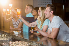 Group of friends holding glass of beer in party. Group of smiling friends holding glass of beer in party at bar stock photo