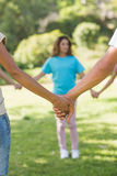 Group of friends holding hands in park Stock Photo