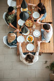 Group of friends holding hands and saying prayers. Top view of a group of friends holding hands and saying prayers while having dinner at the table at home royalty free stock photo