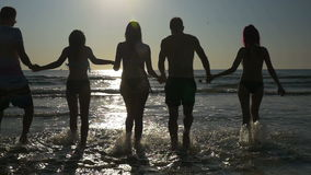 Group of friends holding hands and walking in the sea at twilight in slow motion. Group of friends holding hands and walking towards the sea at twilight in slow stock video footage